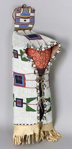 Central Plains Fully Beaded Hide Cradle, Lakota, c. last quarter 19th century, the soft hide form with rawhide tab at the upper back, with multicolored and metallic geometric devices on a white ground, further decorated with strings of bugle beads with cowrie shell and brass hawk bell danglers