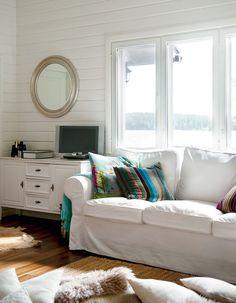 Vaaleat värit luovat mökin pienistä tiloista raikkaat ja tilavan tuntuiset. Värilliset tekstiilit tuovat sopivasti kontrastia sisustukseen.