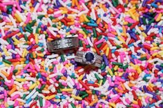 Wedding rings resting in rainbow colored ice cream sprinkles - www.kphotosphotography.com