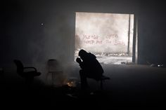 Photos of the day - January 28 2017Refugee Samiuallah Ahmadi...  Photos of the day - January 28 2017  Refugee Samiuallah Ahmadi 18 from Kabul Afghanistan warms himself around a fire in an abandoned warehouse in Belgrade Serbia; Protesters assemble at John F. Kennedy International Airport in New York after two Iraqi refugees were detained while trying to enter the country.; A man takes a photograph of his friend as thick smoke rises from a fire which broke out at oil wells set ablaze by…