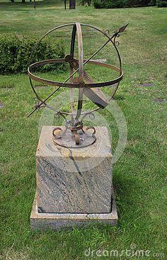 A iron arrow armillary sphere sundial rests on a marble base.