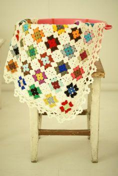 Crocheted baby blanket 80 x 80 cm in little squares.  Colours : cream, fushia, light pink, dark grey, light grey.
