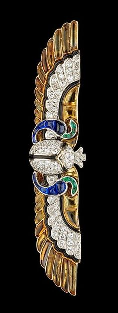 Egyptian-themed scarab brooch by Cartier, ca.1920. Diamonds, sapphires, emeralds and onyx set in yellow gold