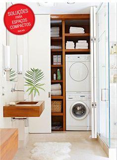 """Já este banheiro, com um pouco mais de espaço, foi possível colocar um armário, que """"esconde"""" tanto a lavadora quanto a secadora, além de outros acessórios da área de serviço."""
