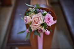 Little bouquet in pastel colours from beautifoul roses as pew arrangement for wedding.