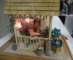 """Front View of a garden retreat """"Jennett's Shabby Chic Retreat"""" in 1:12 scale, exhibited by Janet M. Oliver at the Spring 2014 Seattle Dollhouse Show."""