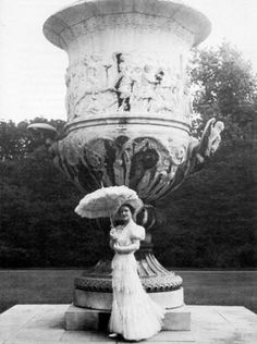 Queen Elizabeth the Queen Mother, 1939. The Queen is photographed by sir Cecil Beaton in front of the monumental Waterloo Vase in the garden of Buckingham Palace. Her outfit is one of Norman Hartnell's creations.