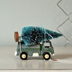 Tiny vintage toy truck with vintage Christmas tree tied on top.