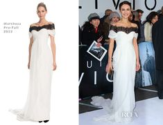 Perhaps in homage to the snowfall we have been experiencing in London today, (April 4, 2013) Olga Kurylenko took to the red carpet at the BFI IMAX in London this evening as Snow White for the 'Oblivion' premiere.  She wore a winter-white Grecian-style Marchesa Pre-Fall 2013 off-the-shoulder gown, featuring a contrast re-embroidered black lace and sheer neckline, gathered sweetheart bodice, and a draped full-length skirt.