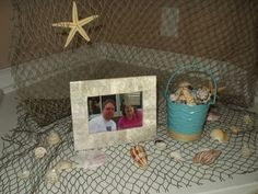 Use net to hang photos of wedding couple - accent with shells