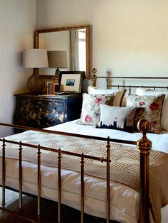 Gold bedframe with cream bedding and floral cushions - love the distressed dresser too!
