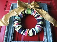 Cute wreath made out of sock over a foam core! How cute and soooo many possibilities!  Orange and black girl knee socks or ladies tights legs for halloween. Pink and white for Valentines Day. Cute factor could go waaaay up with cute embellishments and a wild bow!