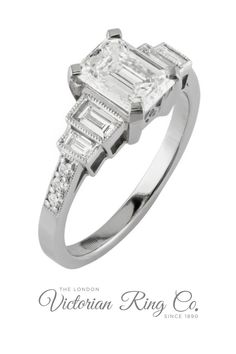 This impressive Art Deco style emerald-cut diamond engagement ring is set with three diamond shapes: a rectangular shaped emerald cut diamond, two baguette cut diamonds on either side of the main diamond and the band is set with six round diamonds. #diamondengagementring #diamondring #artdecostyleengagementring #emeraldcutdiamondring #baguettediamond #emeraldcutengagementring