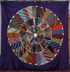 "Silk/satin neck tie quilt. ""Wheel of Fortune"" design. Two edges are rolled over with a hand sewn blanket stitch."