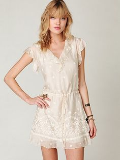 Sleeveless sundress with delicate floral embroidery and plunging, ruffled v-neckline in the front and back.