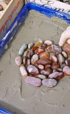 Jetzt beginnt der kreative Teil der Arbeit: Legen Sie die Kieselsteine nach Lust und Laune aus – kreisförmig, diagonal oder in Mustern – ganz nach Ihrem persönlichen Geschmack (links). Drücken Sie die Steine dabei leicht in den Mörtel hinein. Ist das Muster fertig, kontrollieren Sie, ob alle Steine gleichmäßig weit herausragen und gleichen Sie die Höhe gegebenenfalls mit einem Holzbrett etwas aus. Anschließend wird das Mosaik mit dünnflüssigem Mörtel ausgegossen (rechts) und an einem…