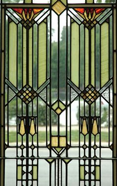 Prairie School stained glass window in a geometric design in green, yellow, and clear glass.