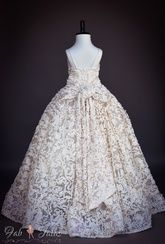 Reverie dress features off white/ivory textural lace with silver cording, fitted bodice with elasticized insert in the back, gorgeous skirt with full tulle underskirt, rhinestone applique up front and an oversized bow in the back. Fully lined. Dry clean only.