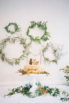 greenery wreaths as a dessert table backdrop and some greenery for the cake display