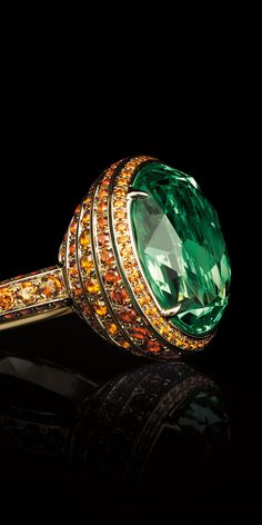 An 18k yellow gold basket of spessartites highlights the allure of an 11.79-carat oval light tsavorite in this exquisite ring.