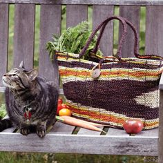 Get back to nature with this carryall. Hand woven from plied pandanus leaf dyed in earthy orange, yellow and brown colors with coconut shell button closure. Fiber-wrapped handles and flat base ensure comfort and stability. 11in. h x 24in. w x 8in. d, handles: 18in. l