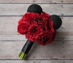 This Disney inspired silk wedding bouquet is perfect for the bride who loves Mickey! Red roses and ranunculus are accented with Mickey ears, and wrapped with black satin. This wedding bouquet is wrapp