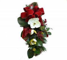 Magnolia Christmas Swag - Add some Style and lively personality to any door with this flower pine swag. Enbelished with a hand made Red Velvet Bow, Magnolia Flowers, Ivy, miniature red berries, medium sized red berries. #ChristmasWreath #ChristmasDecor