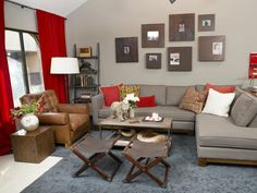 A two-piece sectional allows for plenty of seating in this African-inspired living space. The bright red curtains, metallic gray open back shelving and leather-tufted chair bring warmth and comfort. The steel and wood coffee table is spruced up with a cement bear, candles and flowers to keep the rustic look alive. #livingroom #Africa