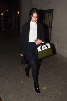 Leaving Lady Gaga's parents' restaurant in New York in a white turtleneck, pleated navy skirt and black coat.    - HarpersBAZAAR.com