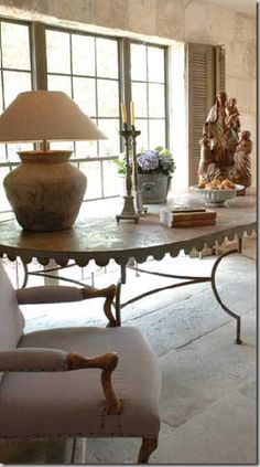 Metal Garden Table in a Houston house built with reclaimed items from Chateau  Domingue – the windows, shutters, stone walls, and floors.