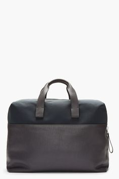"""LANVIN - Dark grey leather and textile duffle Structured textured leather duffle bag in dark grey. Industrial zip at main compartment. Double leather carry handles. Top panel in tonal textile. Welt pocket at back face with concealed magnetized closure. Seam pockets at sides of welt pocket. Tonal textured leather accent panel at front face. Approx. 18"""" length, 8"""" width, 12"""" height. 60% calf leather, 25% polyester, 10% cotton, 5% brass. Made in Spain. $1475 CAD"""