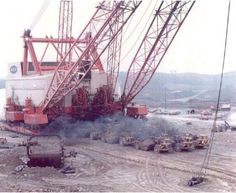 Massive loads.None other then Big Muskie.The Bucyrus Erie 4250W walking dragline that weighed 28 million pounds & swung a 220 cubic yard bucket.What is going on here is that many Caterpillar scrapers are pulling  turntable out from underneath Big Muskie to be repaired