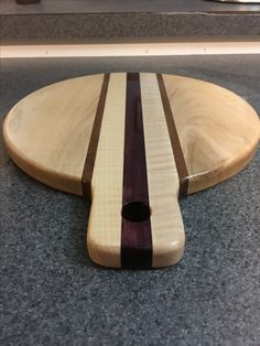 Curly Maple circular cutting board with Mahogany and Purple Heart accent pieces and a handle for easy pickup.