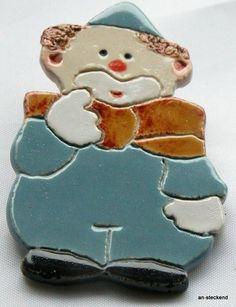 Brosche *Clown mit Schleife* <p>Ein tolles Geschenk für viele Anlässe! Der liebe kleine Clown gratuliert ganz herzlich.  <br>  <br>  Die *an-steckend*-Broschen wurden in aufwändiger Handarbeit hergestellt: Zuerst wurde der Ton geschlagen um Luftblasen zu entfernen, dann hauchdünn ausgerollt, nach selbst entworfenen Vorlagen ausgeschnitten, geglättet, getrocknet, rohgebrannt, glasiert, noch einmal gebrannt und schließlich mit einer Sicherheitsbroschennadel versehen.<br>  Obwohl diese…