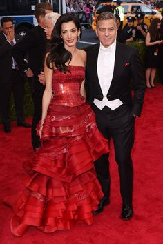 Amal (in a red ruffled Maison Margiela number by John Galliano) and George Clooney hit the red carpet arm-in-arm.