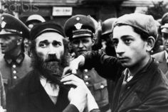 Jewish Boy Cuts Father's Beard Near Nazi Soldiers. The vacant look to his eyes illustrates his distaste for what he is doing.