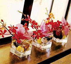 Centerpieces: These are delicate Ikebana style flower arrangements in square vases. We like that they are small and compact, but also with upward motion.