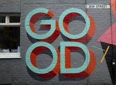 """Graffiti art sign on a gray brick wall on Jew Street that reads """"GOOD."""""""