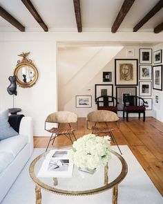 Wide-plank floors, brass accents, gallery wall with photographs, drawings, etc.