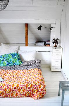 bedroom. rustic modern. simple. white with brightly colored bed linens. white painted wood planks. industrial pieces (file cabinet, fan, steel table/stool).