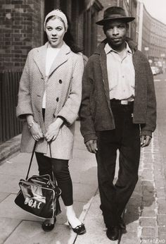 A West Indian man and his girlfriend walk through the streets of Notting Hill Gate, London despite the threat of right-wing thugs in the area, 2nd September, 1958