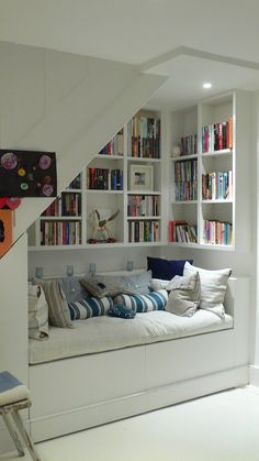 utilize spaces under stairs with wall built in bookshelf and bench seat as reading and lounge room ideas under stairs