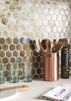 Genau (top) and Voni (bottom), iridescent glass mosaic tiles, both from Original Style. They work well with a crisp white worktop and on-trend copper accessories.