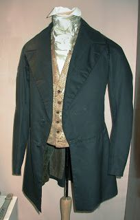 Frock Coat, Waistcoat, Shirt, and Cravat The coat is from 1845-1855 and is made of a fine black broadcloth. It is double-breasted, has very wide notched lapels and is entirely hand stitched. The skirt and side back are lined with greenish wool or mohair brocade. The front and sides are padded and there are no pockets except for 2 hidden in the back. The buttons are cut velvet covered and the sleeve vents have 3 small satin covered buttons.   The Greene Collection-Genesee Country Village…