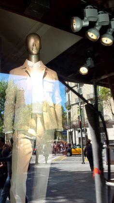 ADOLFO DOMINGUEZ. Passeig de Gràcia, 32. Moda y complementos para hombre, mujer y niños en cadena de tiendas de ropa y calzado de diseño propio. El escaparate se presenta oscuro con una iluminación directa hacia la prenda puesta sobre un maniquí.