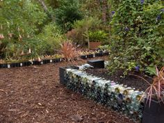 Such a cute idea! A small little retaining wall for your garden made from beer bottles.