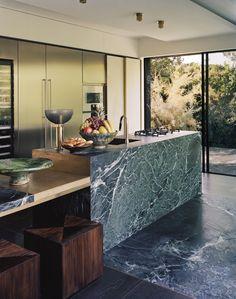 Dans la cuisine, un seul marbre, du sol à l'îlot central. Au marbre Verde Alpi, le décorateur confronte les brillances du laiton et du métal ainsi que la chaleur du bois.