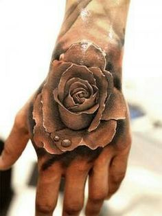 Incredibly realistic grey scale rose tattoo on top of the hand. Love this.