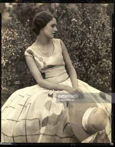June Collyer, debutante and actress, sitting in a garden with bushes in background face in profile; wearing a long robe de style dress with window pane and graphic floral print, she holds a wide brim straw hat in her lap; her hair is in a finger wave and pulled into a bun at the nape of her neck - 1927