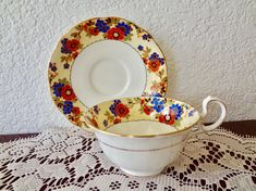 Aynsley Bone China teacup and saucer made in the 1920s. Beautiful teacup measures 2 tall and 3 3/4 wide. The saucer measures 5 1/2 wide. Pretty flowers in colors of rust, tan, black and blue over a pale yellow rim really stand out on the white bone china. Gold trim. Wonderful vintage